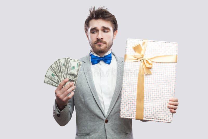 Hombre barbudo joven de la tristeza en traje gris y situación azul de la corbata de lazo y pensamiento que no quieren gastar los  imagen de archivo libre de regalías