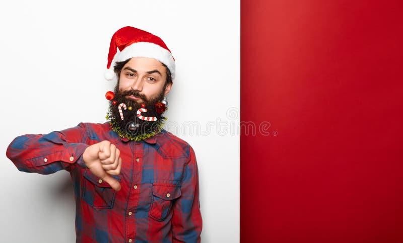 Hombre barbudo joven decepcionado que lleva el sombrero de santa imagen de archivo libre de regalías