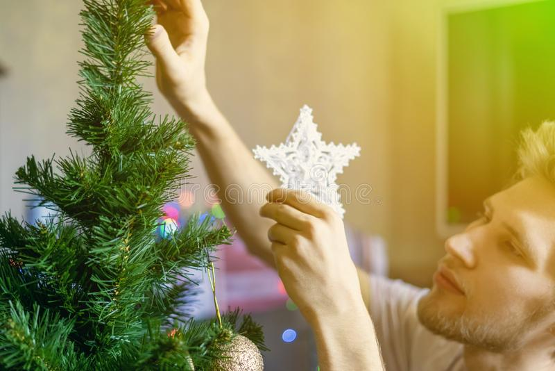 Hombre barbudo joven en casa que hace la preparación nacional al concepto f de los días de fiesta del Año Nuevo de la Navidad fotografía de archivo libre de regalías