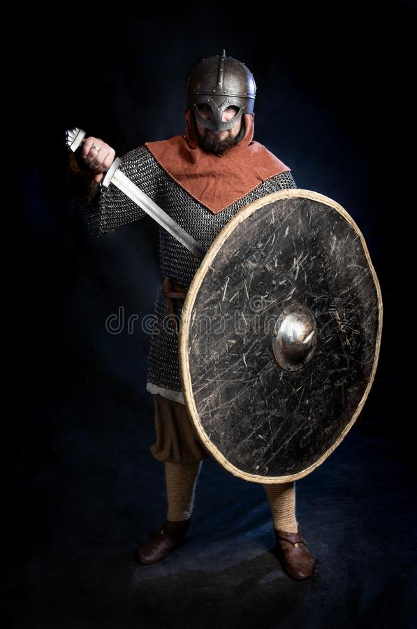 Hombre barbudo joven en un standind y sostener del casco de la Viking-era una espada y un escudo foto de archivo