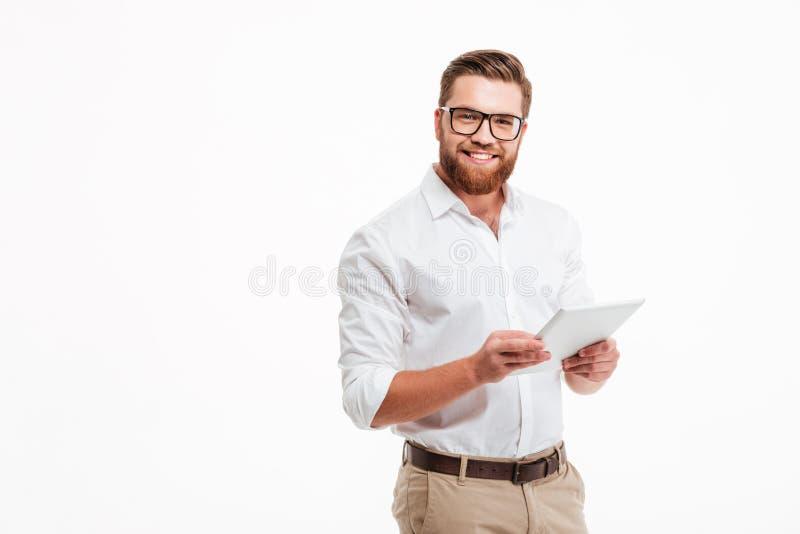 Hombre barbudo joven feliz que usa la tableta imágenes de archivo libres de regalías