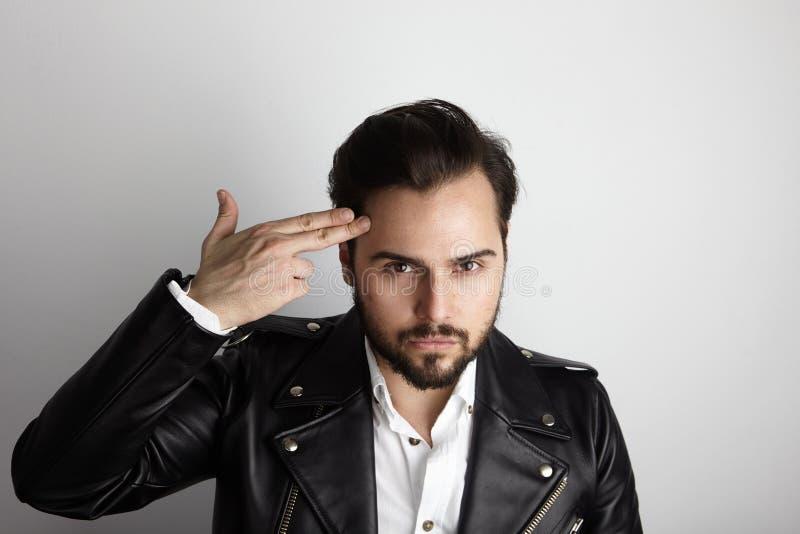 Hombre barbudo joven hermoso que lleva la cabeza elegante de la mano del tiro de la chaqueta de cuero del negro de la camisa Bell foto de archivo