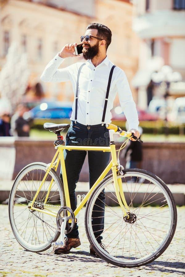 Hombre barbudo joven que habla en el teléfono móvil y que sonríe mientras que se sienta cerca de su bicicleta en calle foto de archivo