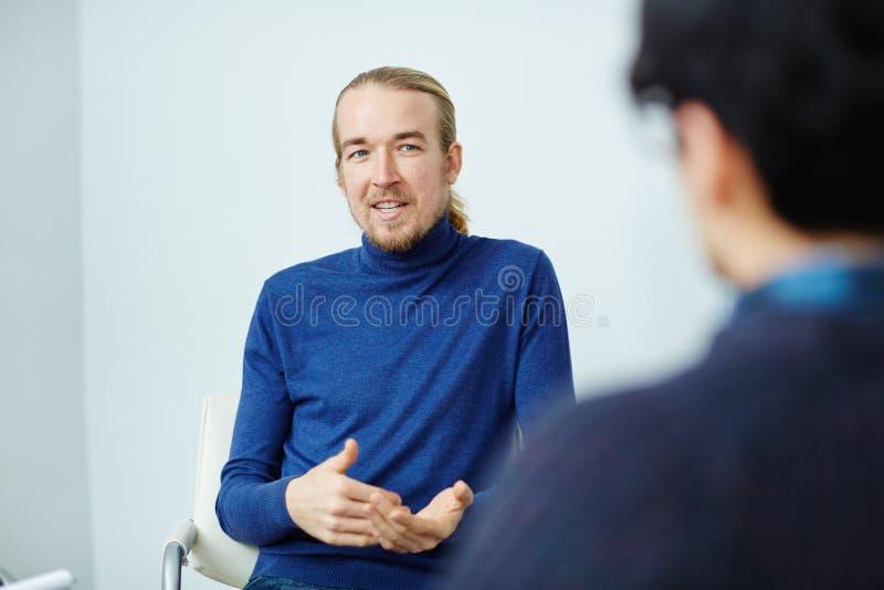 Hombre barbudo joven que habla en la reunión fotos de archivo