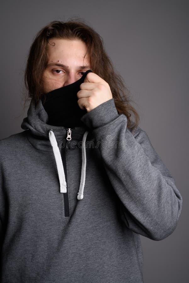 Hombre barbudo joven que lleva sudadera con capucha y la máscara grises contra la parte posterior gris imagenes de archivo