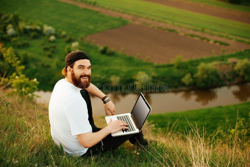 Hombre barbudo joven que trabaja en el ordenador portátil al aire libre fotos de archivo