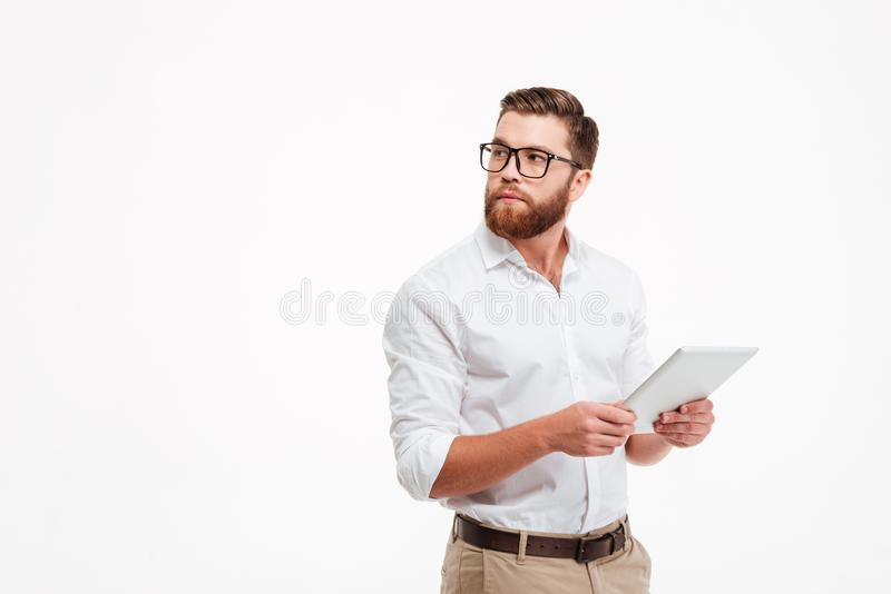Hombre barbudo joven serio que usa la tableta imágenes de archivo libres de regalías