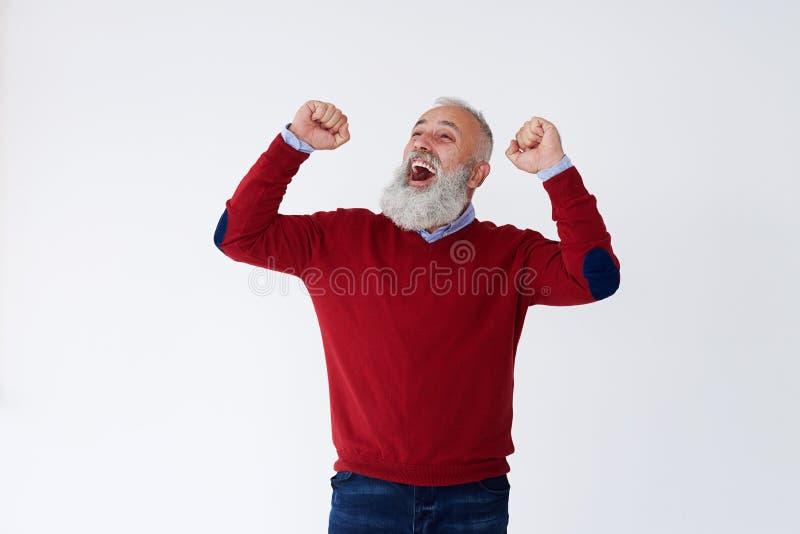 Hombre barbudo maduro feliz que aumenta las manos que miran hacia arriba, celebrat fotografía de archivo libre de regalías