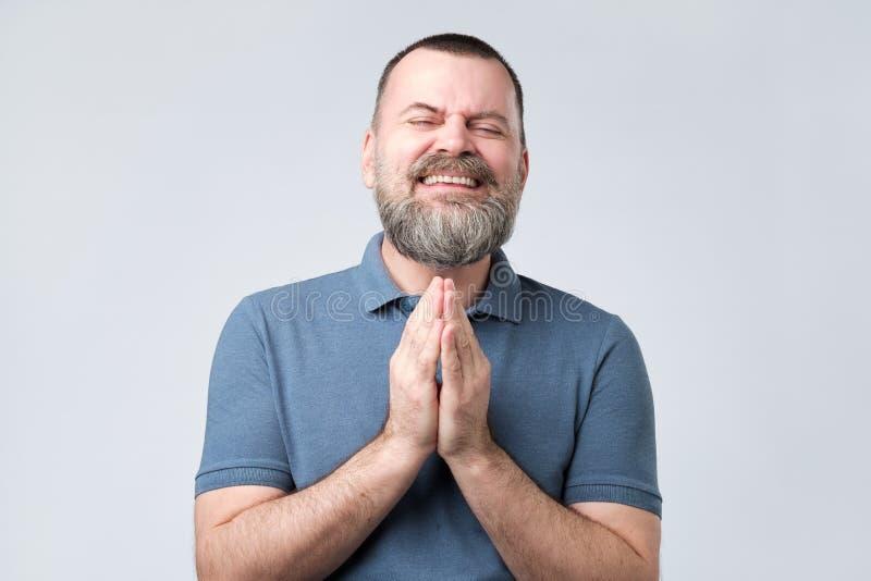 Hombre barbudo maduro unirse a las manos junto que piden pedir ayuda del perdón fotos de archivo