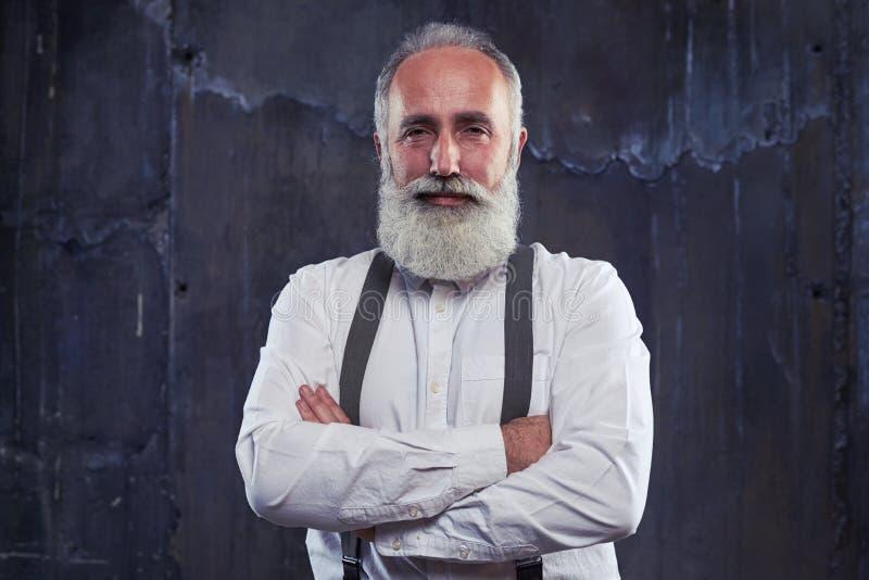 Hombre barbudo mayor hermoso con los brazos doblados sobre fondo imágenes de archivo libres de regalías