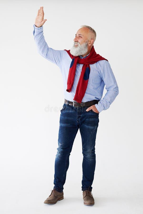 Hombre barbudo mayor sonriente que agita para alguien en sideway fotos de archivo