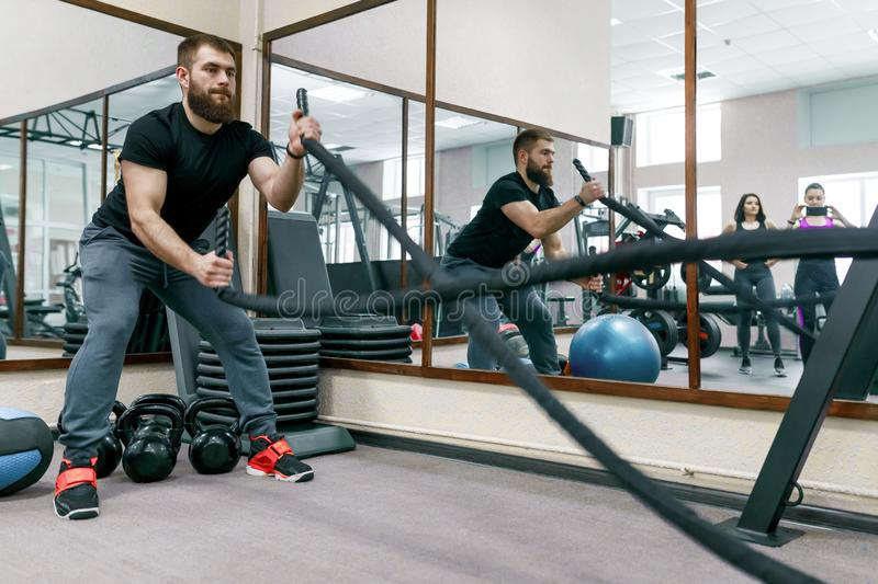 Hombre barbudo muscular atlético que ejercita en el gimnasio con las cuerdas de la batalla Deporte, entrenamiento, gente, concept imagenes de archivo
