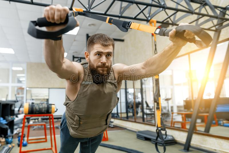 Hombre barbudo muscular vestido en el chaleco acorazado cargado militares que hace ejercicios usando sistemas de las correas en e imagen de archivo