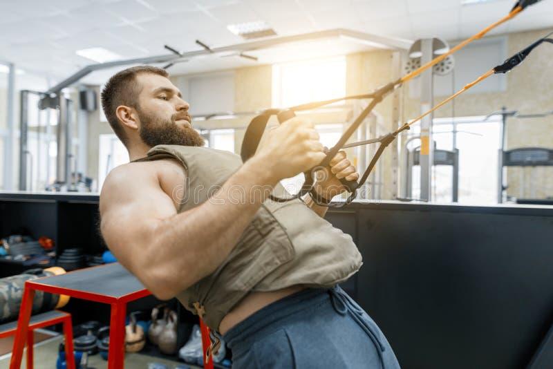 Hombre barbudo muscular vestido en el chaleco acorazado cargado militares que hace ejercicios usando sistemas de las correas en e fotos de archivo