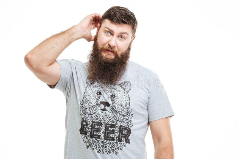 Hombre barbudo pensativo confuso que rasguña su cabeza imagen de archivo libre de regalías