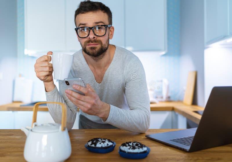 Hombre barbudo que desayuna en la cocina y que usa smartphone imagenes de archivo