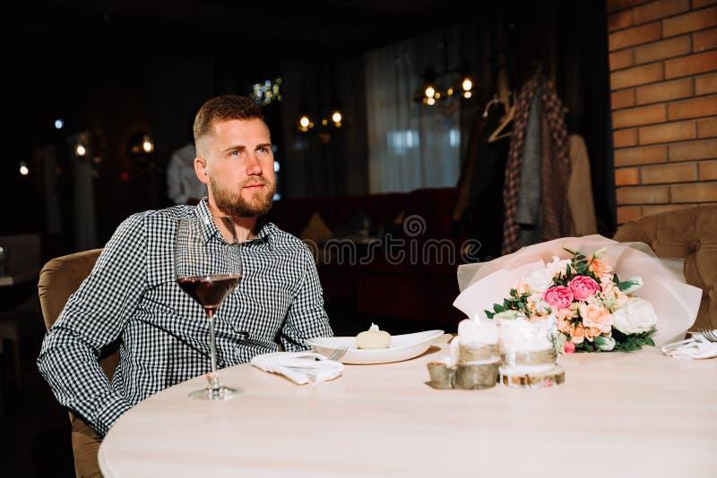 Hombre barbudo que espera a una muchacha una fecha en un restaurante imagen de archivo libre de regalías