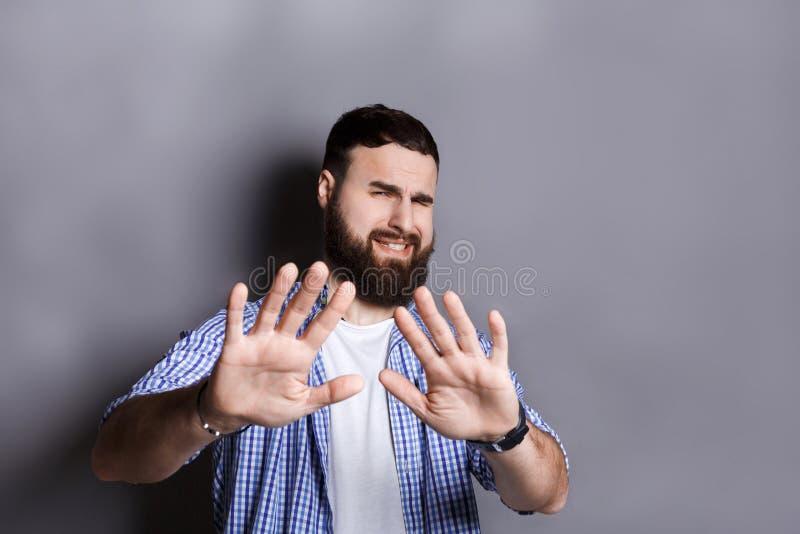 Hombre barbudo que expresa el repugnancia, haciendo muecas imagen de archivo