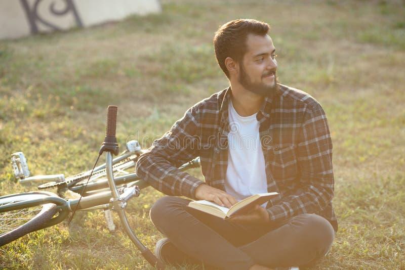 Hombre barbudo que lee un libro, sentándose en hierba cerca de la bici en el parque fotografía de archivo libre de regalías