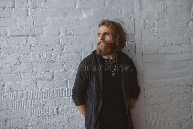Hombre barbudo que lleva la situación gris de la sudadera con capucha fotografía de archivo libre de regalías