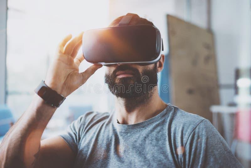 Hombre barbudo que lleva los vidrios de la realidad virtual en estudio coworking moderno del diseño interior Smartphone usando co imagen de archivo libre de regalías
