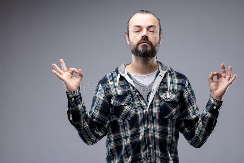 Hombre barbudo que medita con una expresión serena imagen de archivo libre de regalías