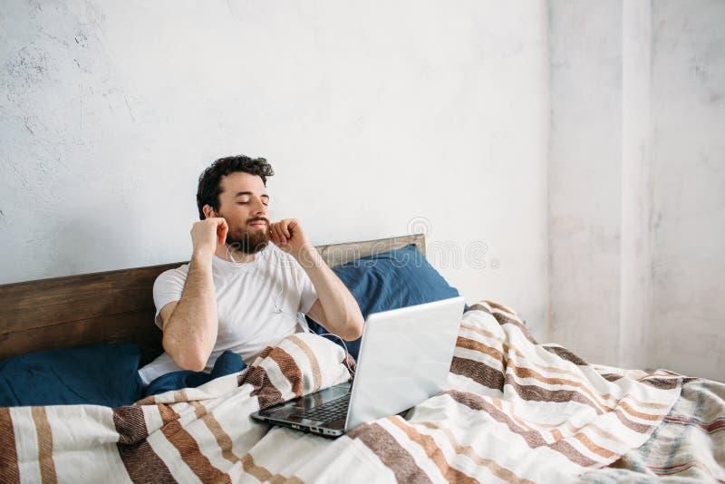 Hombre barbudo que miente en cama de la mañana con el ordenador portátil imagen de archivo