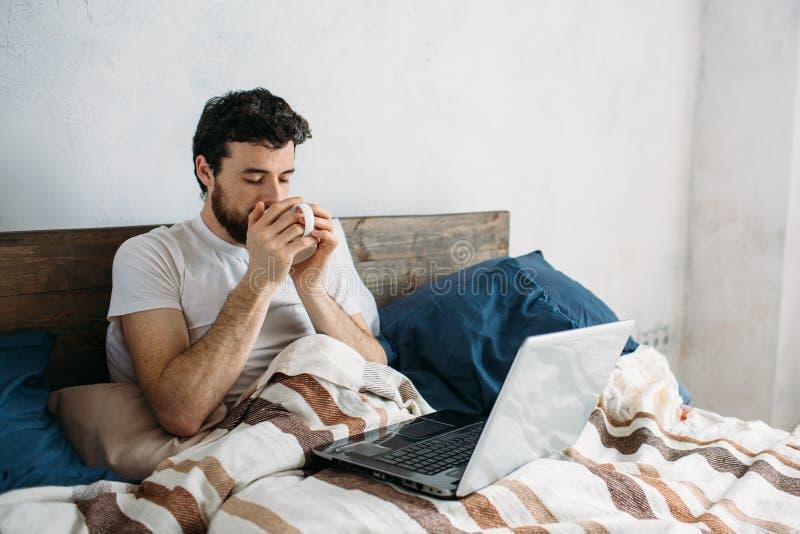 Hombre barbudo que miente en cama de la mañana con la taza del café o de té fotografía de archivo libre de regalías
