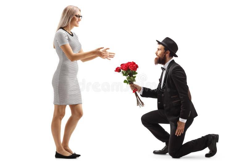 Hombre barbudo que se arrodilla y que da un ramo de rosas rojas a una mujer fotos de archivo libres de regalías
