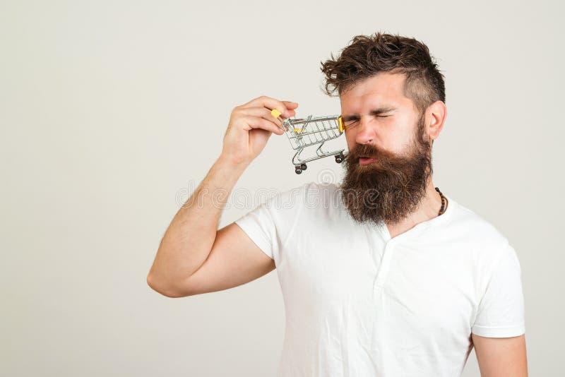 Hombre barbudo que se ríe con el pequeño carro de la compra Colisión hermosa del hombre con la carretilla que hace compras Venta, fotos de archivo libres de regalías