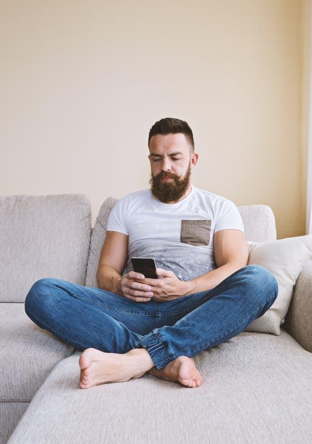 Hombre barbudo que se sienta en el sofá con smartphone imagenes de archivo