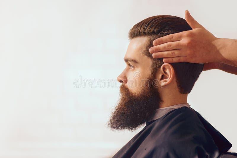 Hombre barbudo que se sienta en la barbería foto de archivo libre de regalías
