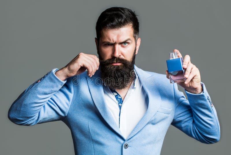 Hombre barbudo que soporta la botella de perfume Botella del cologne de la moda El varón barbudo prefiere el olor costoso de la f foto de archivo