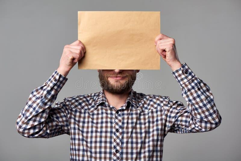 Hombre barbudo que sostiene el sobre marrón en blanco foto de archivo