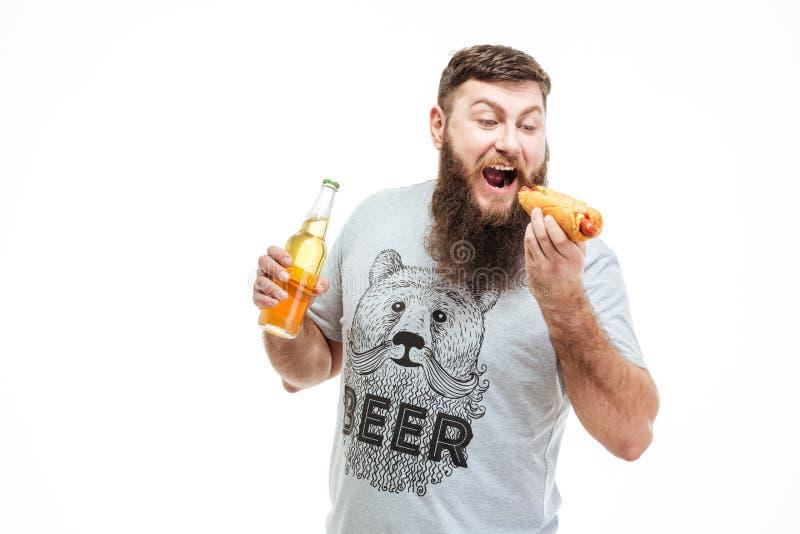 Hombre barbudo que sostiene la botella de cerveza y que come el perrito caliente fotografía de archivo libre de regalías