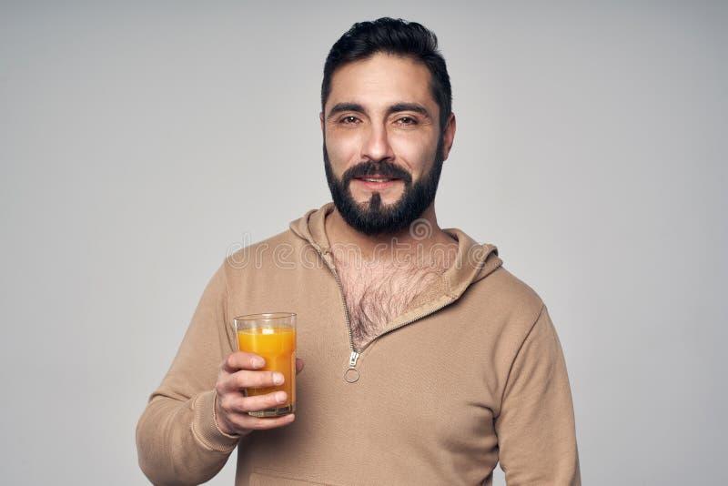 Hombre barbudo que sostiene un vidrio de zumo de naranja foto de archivo libre de regalías