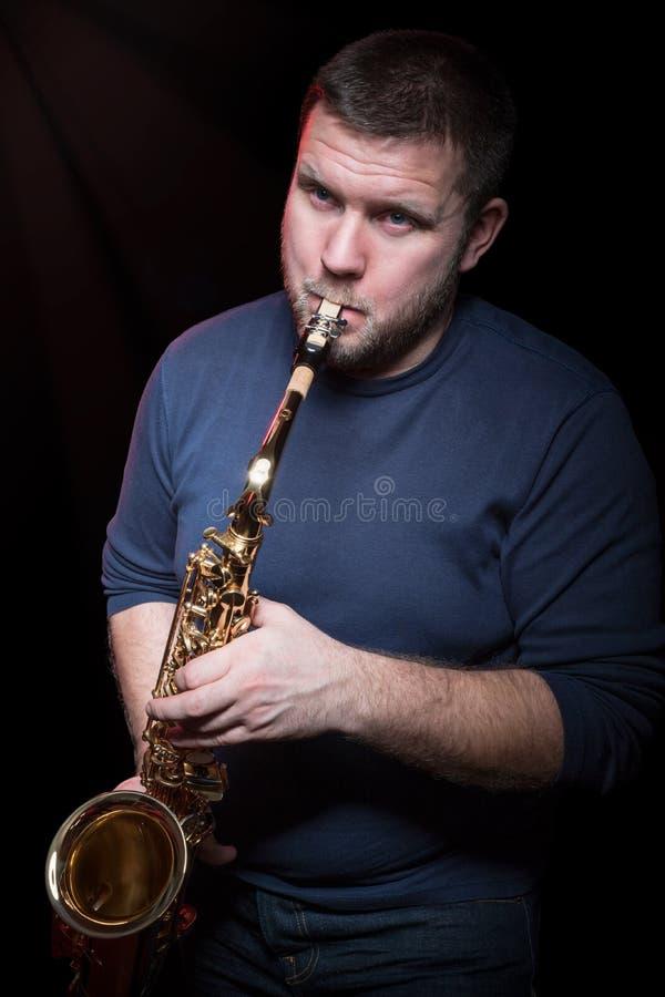 Hombre barbudo que toca el saxofón foto de archivo