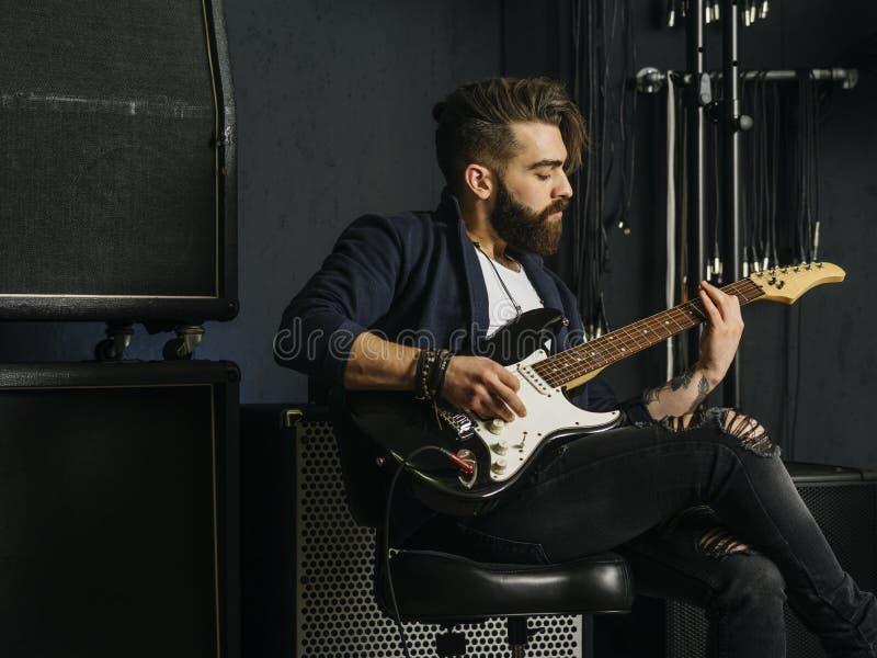 Hombre barbudo que toca la guitarra en un estudio de la música fotografía de archivo