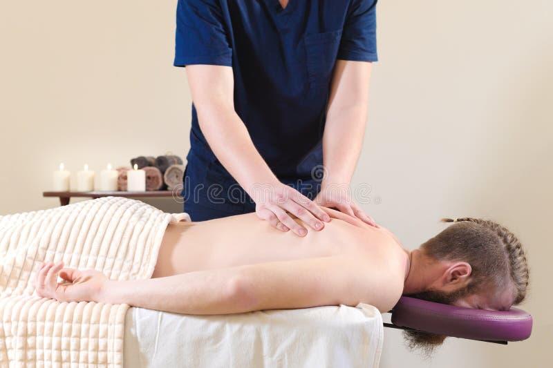 Hombre barbudo relajado con un corte de pelo elegante en la recepción en el quiropráctico Procedimiento del masaje de la salud fotos de archivo