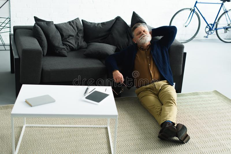 hombre barbudo relajado que se sienta en la alfombra y que se inclina en el sofá imagenes de archivo