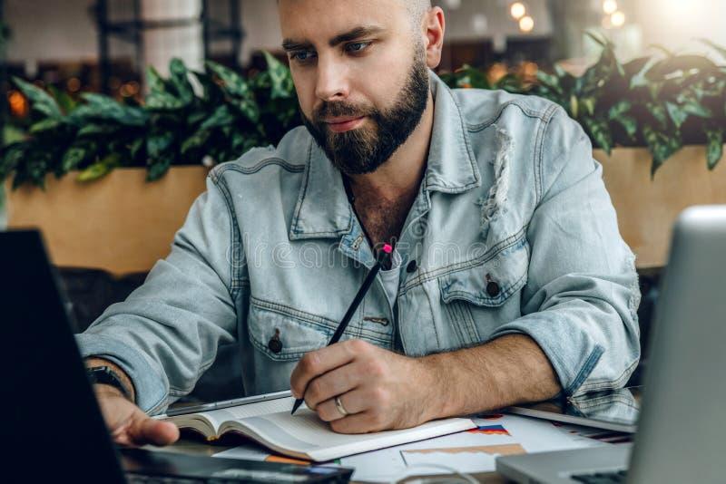 Hombre barbudo serio del inconformista que se sienta en oficina, haciendo notas en el cuaderno, trabajando El empresario analiza  fotografía de archivo