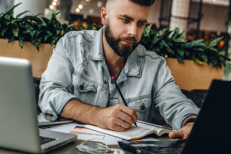 Hombre barbudo serio del inconformista que se sienta en oficina, haciendo notas en el cuaderno, trabajando El empresario analiza  imagen de archivo