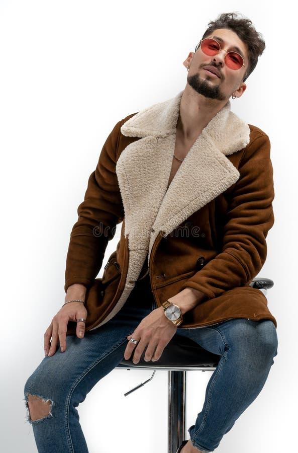 Hombre barbudo serio en ropa elegante casual y gafas de sol rojas que se sientan en el taburete de bar, mirando la c?mara aislada fotos de archivo