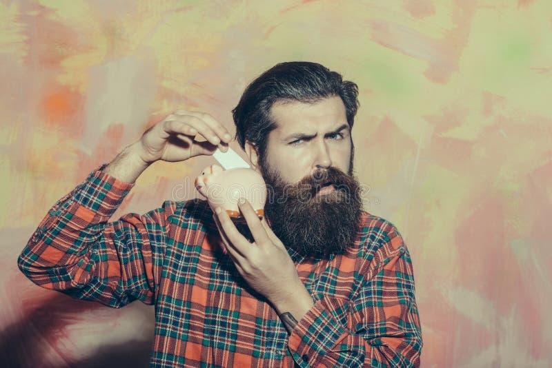 Hombre barbudo serio que pone el billete de banco en la hucha de cerámica rosada foto de archivo