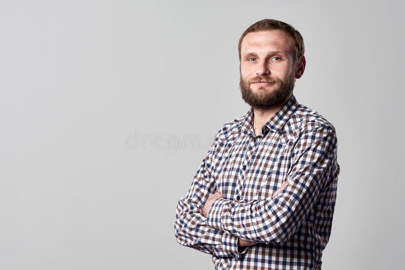Hombre barbudo serio que se coloca con las manos dobladas fotografía de archivo libre de regalías