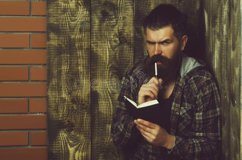 Hombre barbudo serio que toma la nota en cuaderno con la pluma foto de archivo libre de regalías