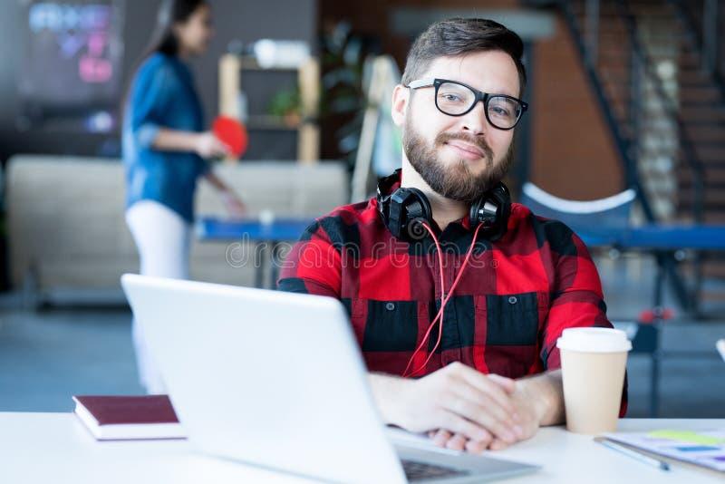 Hombre barbudo sonriente en oficina de las TIC foto de archivo libre de regalías