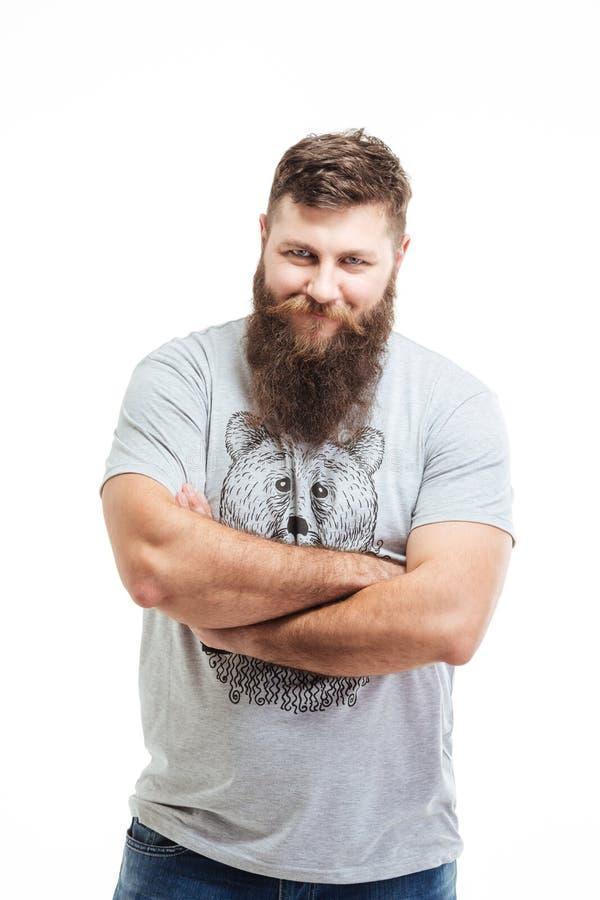 Hombre barbudo sonriente hermoso que se coloca con los brazos cruzados foto de archivo libre de regalías