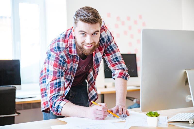 Hombre barbudo sonriente que se coloca y que trabaja en modelo en oficina fotos de archivo libres de regalías