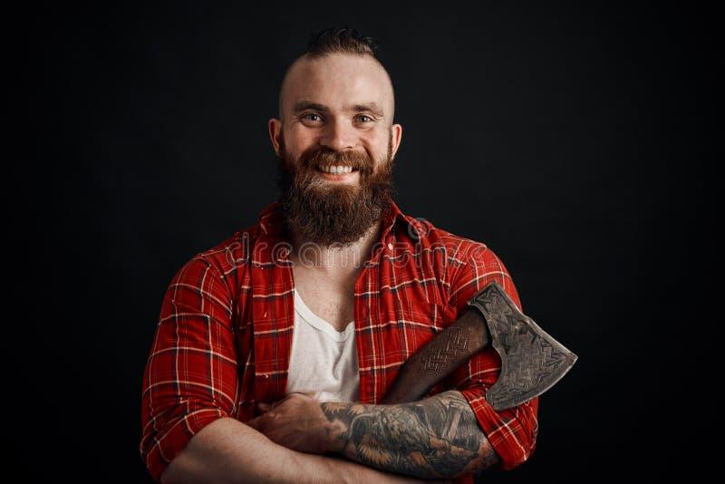 Hombre barbudo sonriente que sostiene el hacha que mira la cámara en fondo negro imagenes de archivo